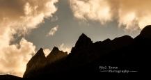 The sun streams between the gap of the twim peaks of Asses Ears