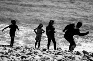 Family skimming stones capturing the essence of a British Beach holiday.