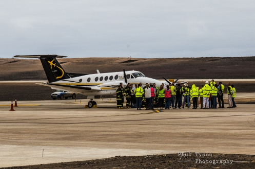 Dignitaries, staff and others gathered around the plane and crew.