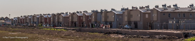 An attempt to improve Cape Towns housing crisis with cheap apartments on the edge of the shanty town.